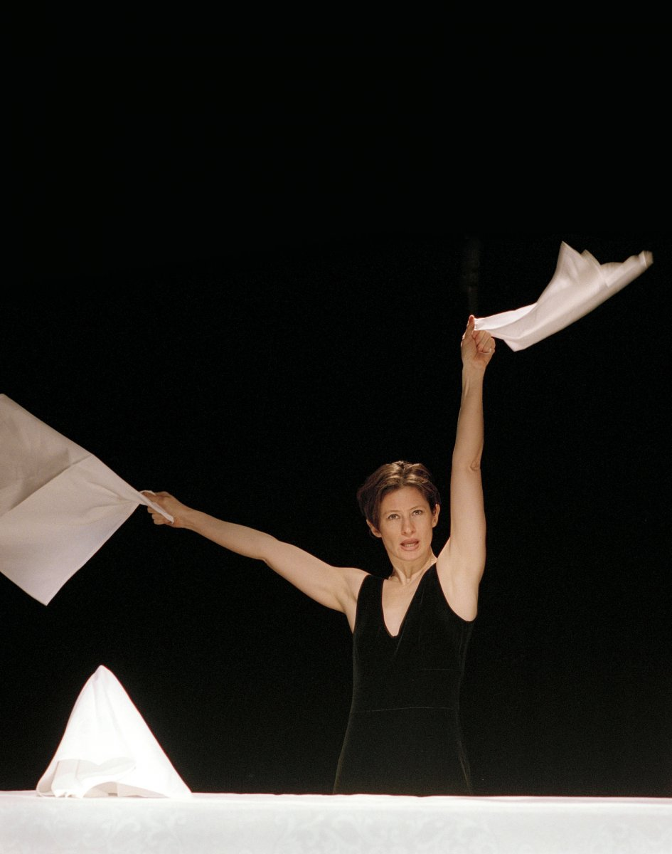 Woman sending a semaphor message using white sheets during a performance
