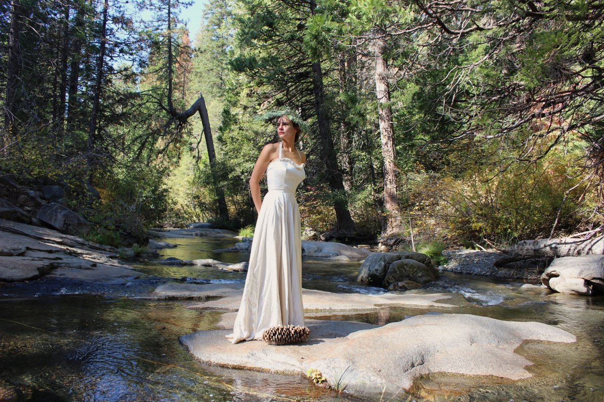 Woman wearing a sugar pine wreath and floor-length white dress stands on a rock in a forest stream